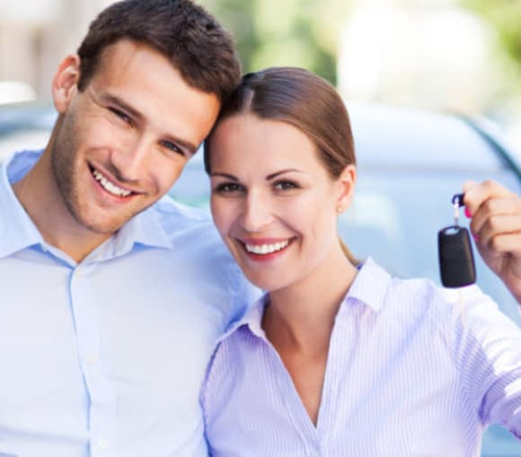 happy couple holding a car key